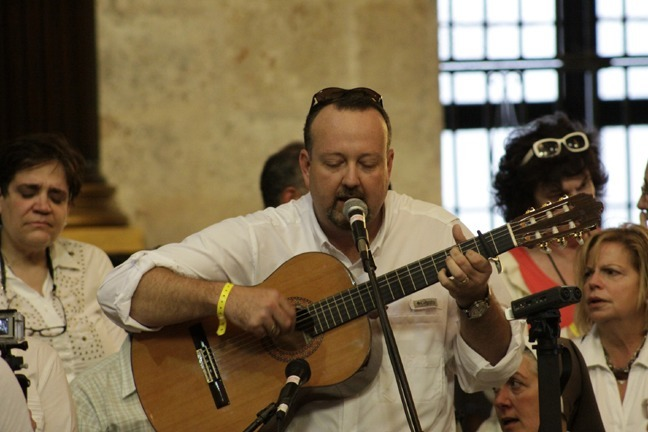 Miami pilgrim Manny Garcia-Tunon leads the singing during the Mass celebrated by Archbishop Thomas Wenski in Havana's cathedral.