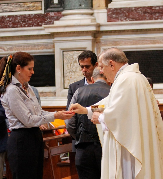 Pilgrim Vicky Yardley of Assumption Church receives Holy Communion from Archbishop Thomas Wenski.