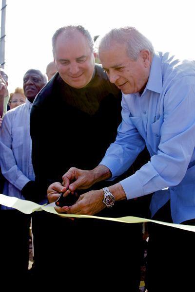 El Padre Juan Rumin Dominguez y el alcalde de la ciudad de Miami, Tomás Regalado, cortan la cinta de inauguración durante la ceremonia.
