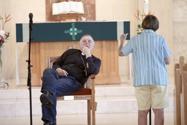 Wearing jeans and Harley-Davidson riding shoes after riding to the Keys in his motorcycle, Archbishop Thomas Wenski listens to participants in the Florida Keys synod listening session.
