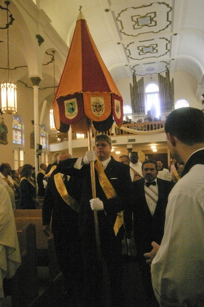 Knights of Columbus carry the ombrellino, one of the insignia of a basilica, into St. Mary Star of the Sea at the start of the dedication Mass. At center: Andy Kirby, with Chris Weber at left and Robert DeLauro at right