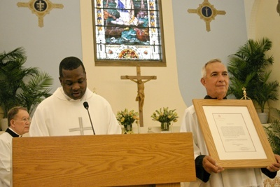 Father Chanel Jeanty, archdiocesan chancellor for canonical affairs, reads the Vatican document conferring the status of a minor basilica on St. Mary Star of the Sea in Key West, as a parishioner Tony Herce serving as an acolyte holds up the framed original.