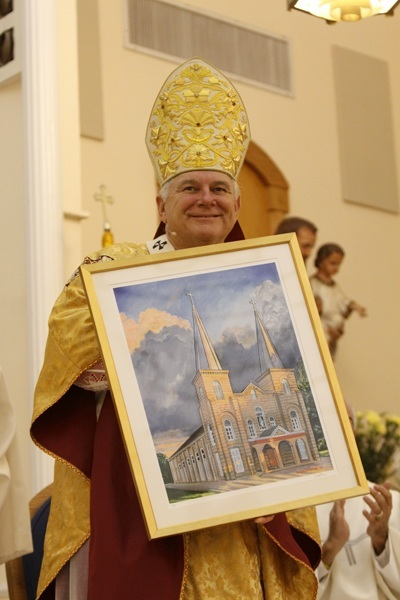 Archbishop Thomas Wenski shows off the first print of a specially commissioned painting of the new basilica, created by Key West artist Richard Matson.