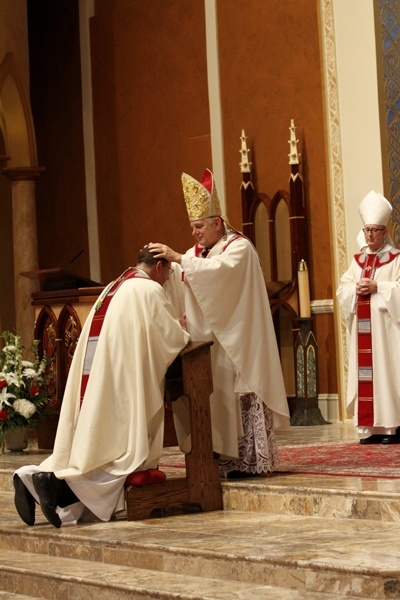 Archbishop Thomas Wenski lays hands on Bishop Gregory Parkes, during the rite of ordination of a bishop.