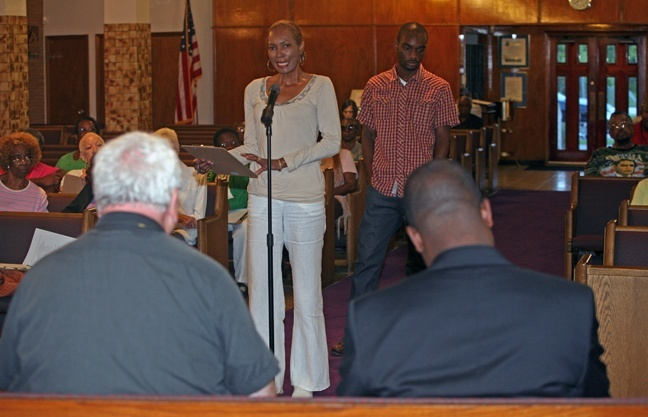 Verna Pegues addresses Oblate Missionary Father John Cox, left, and Father Chanel Jeanty.