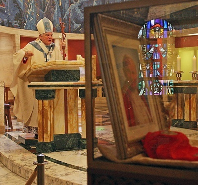 Archbishop Thomas Wenski preaches the homily as a photo of Pope John Paul II and a blood relic are displayed in the foreground.