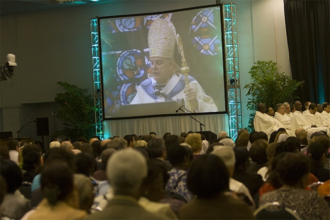 Archbishop Thomas Wenski's image is projected onto one of two large screens during the Synod closing Mass, which was broadcast live by EWTN and livestreamed on the websites of the Archdiocese of Miami and Radio Paz 830 AM.