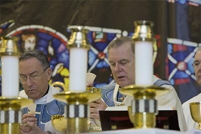 Archbishop Thomas Wenski consecrates the Eucharist with Honduran Cardinal Oscar Rodriguez Maradiaga at his side.