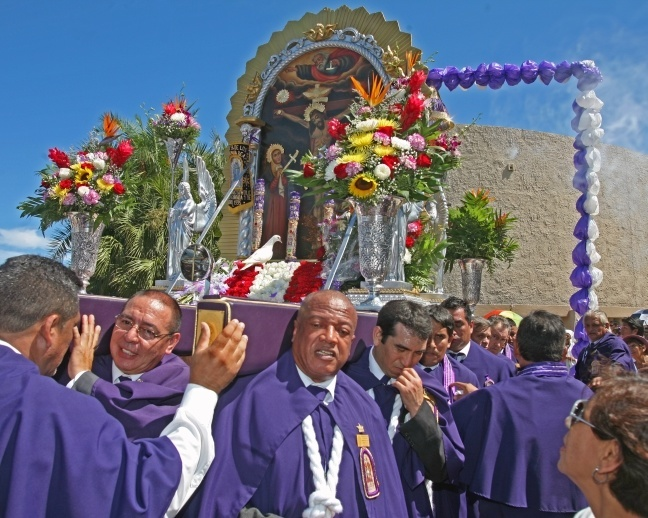 Peruvians celebrated Our Lord of Miracles with a Mass and procession at Holy Family Church, North Miami. Here, members of the Brotherhood of Our Lord of Miracles carry an image of Our Lord as a white dove sits in front.