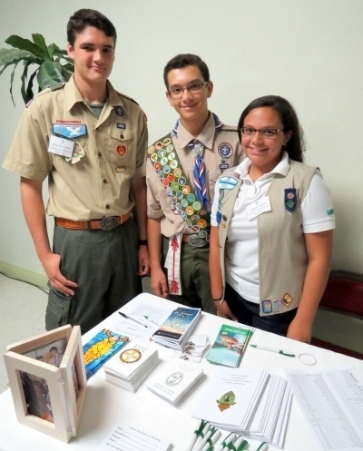 Nicolas Fernandez, Gabriel Seiglie and Isabelle Seiglie pose at the registration table where they spoke with attendees and handed out literature on Catholic Scouting.