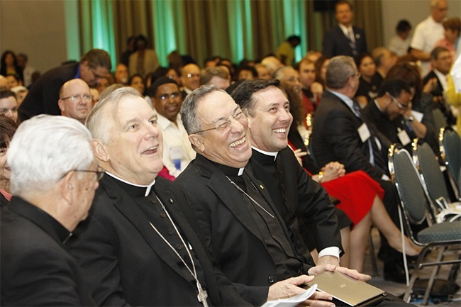 After speaking at the Synod closing assembly, Cardinal Oscar Rodriguez Maradiaga laughs at a joke made by co-master of ceremonies Father Jose Alvarez.