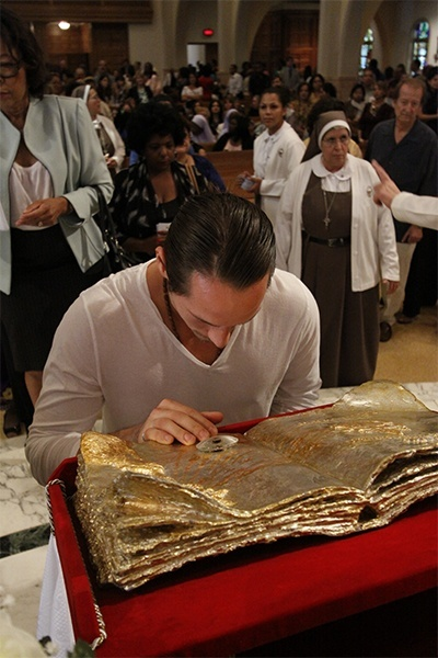 A young man venerates the relic of Pope John Paul II.