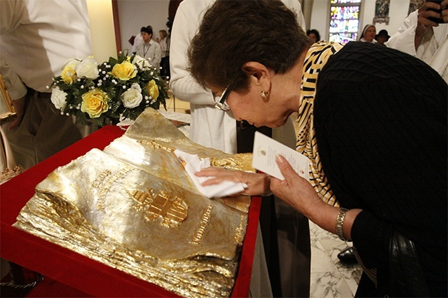 A woman touches a handkerchief to the relic of Pope John Paul II during its first stop in the archdiocese, at St. Mary Cathedral.