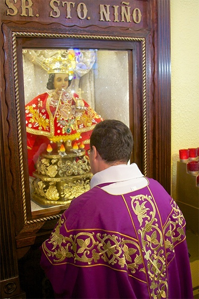 Father Carlos Vega pastor at St. Bernard Church in Sunrise, kneels and prays in front of the image of