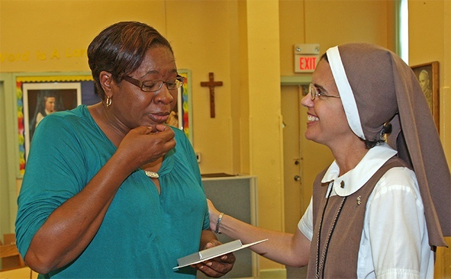 Mimosa Altidor, volunteer teacher, sheds tears as she receives her 0 gift card from Sister Michelle Fernandez of the Servants of the Pierced Hearts of Jesus and Mary, principal of St. Mary Cathedral School.