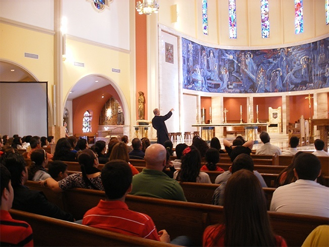 Father Christopher Marino, rector of St. Mary Cathedral, points out the mural that surrounds the sanctuary and explains its significance to parents, sponsors and those preparing to receive confirmation and first Communion this year.
