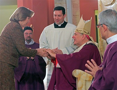 Archbishop Wenski receives the offertory gifts from Joan Crown, archdiocesan director of the respect life ministry.