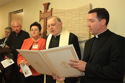 Archbishop Thomas Wenski, aided by his master of ceremonies Father Richard Vigoa, prays during the dedication of the new inpatient Catholic Hospice unit at Holy Cross Hospital.