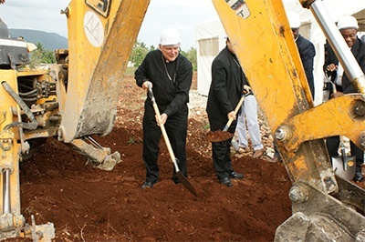 Archbishop Wenski shovels dirt under a large earthmover during the groundbreaking for the new multipurpose building in Jacmel.