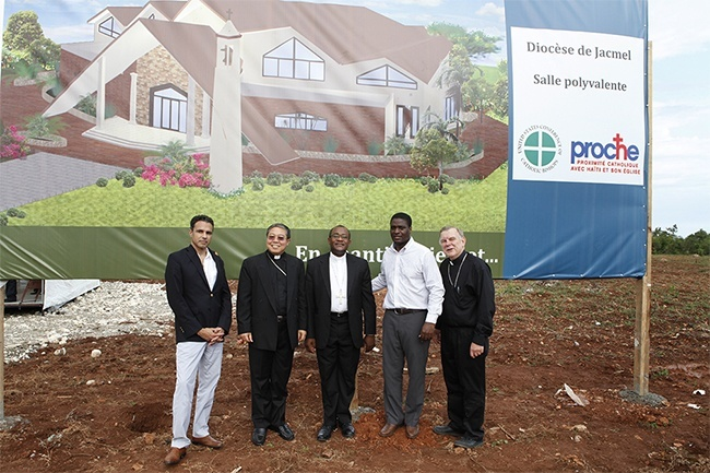 Posing in front of the architect's rendering of the new multipurpose building in Jacmel, from left: Jacques Liautaud, the U.S. bishops' manager for Haiti, Archbishop Bernardito Auza, papal nuncio to Haiti,  Bishop Launay Saturné of Jacmel, Stephan Destin, director general of PROCHE in Haiti, and Archbishop Thomas Wenski.