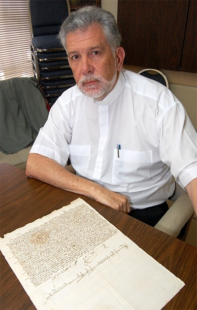 Father Jose Luis Menendez with one of the 10,000 original documents in the historical archive, which also has 400,000 digital copies of documents.