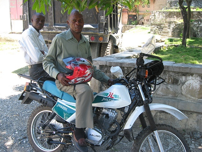 Two of the supervisors of schools in Port-de-Paix, Haiti, Miami's sister diocese sit atop the Chinese-made motorbike that will help them visit schools and train teachers in the remote mountainside schools.