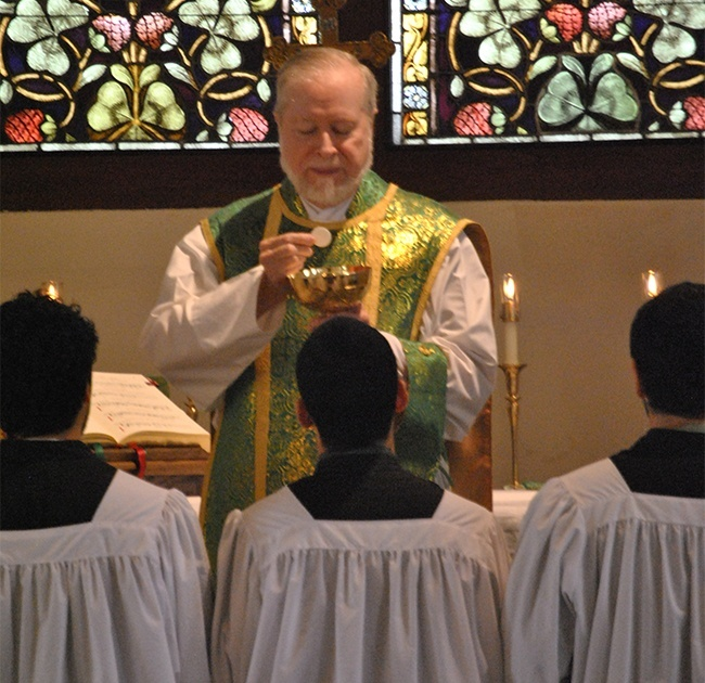Father Joseph Fishwick distributes Communion to altar servers. As an act of reverence, Communion is received kneeling, on the tongue.