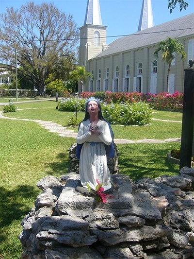 The statue of St. Bernadette faces the grotto and the image of Our Lady of Lourdes as the Basilica of St. Mary Star of the Sea rises in the background.