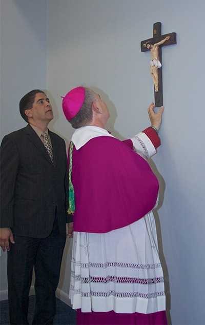 Bishop Fernando Isern, bishop emeritus of Pueblo, Colo.,  places a cross near the entrance of the Christopher Columbus High School's new All Sports Fitness Complex & Bernhardt Wellness Center.
