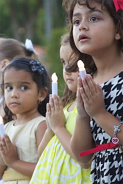 Blessed Trinity School children light the path for the procession that led from Blessed Trinity Church to the newly dedicated Father Joseph T. Carney Enrichment Center. From left are first grade students Karina Martinez, Leah McGregor and Giovanna Khoury.