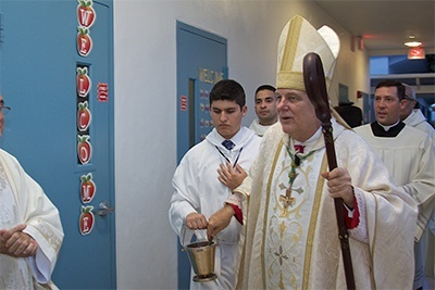 Archbishop Thomas Wenski sprinkles holy water on the exterior walls of the first floor of the Father Joseph T. Carney Enrichment Center.