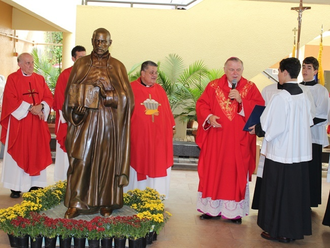 Archbishop Wenski blesses the statue of St. Ignatius Loyola the Teacher in front of invited guests, students and faculty.