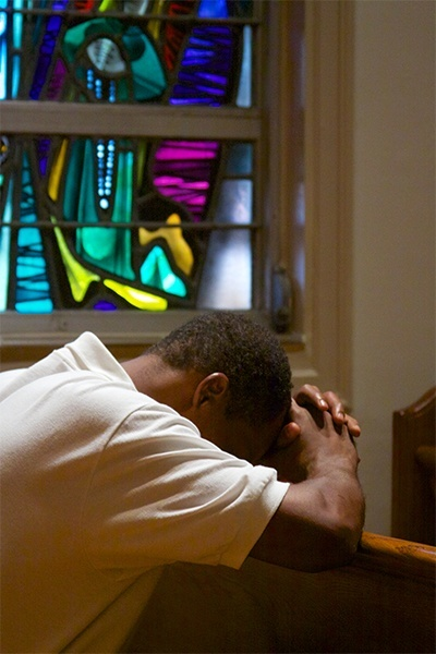 An Emmaus brother prays during the solemn Mass marking the 35th anniversary of the retreat.