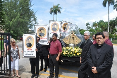 Father Juan Carlos Paguaga, right, pastor of St. John Bosco Church in Little Havana, is accompanied by members of his community as he returns the pilgrim statue of Our Lady of Charity to the shrine on Biscayne Bay. Before the shrine was built, the image smuggled out of Cuba found its first home at St. John Bosco Parish. Every year it returns there the weekend before the start of the novena.