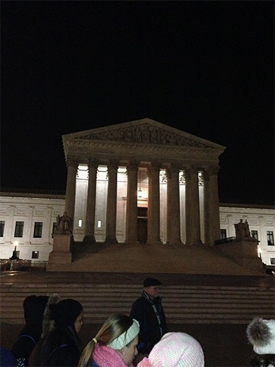 Braving frigid temperatures, high school students from the Archdiocese of Miami take part in an evening prayer vigil in front of the Supreme Court.
