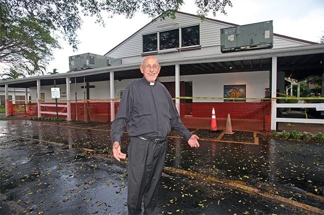 Father Roger Holoubek, pastor, poses in front of the entrance to St. Maurice Church, which is closed off because the awning is sagging.