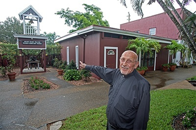 Father Roger Holoubek stands outside the St. Maurice Church complex, formerly Smith's Stables when the parish was founded in 1970.