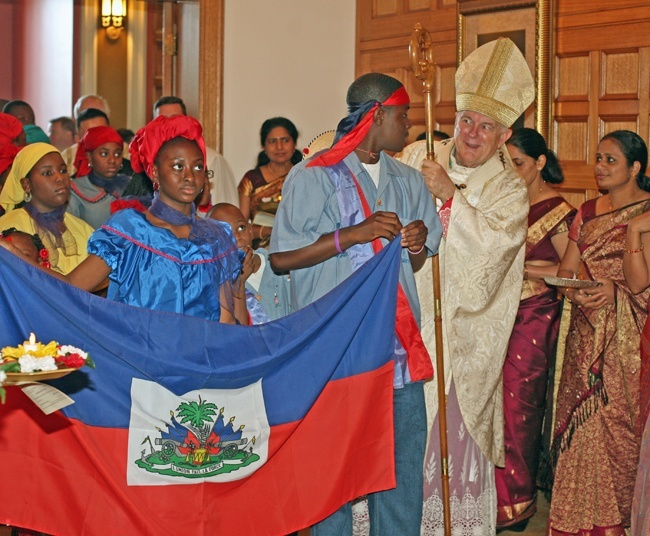 Archbishop Thomas Wenski chats with participants in the processsional for the Migration Mass, including Galvin Decius, 16, as Regine Destin, 13, holds the other end of the Haitian flag.
