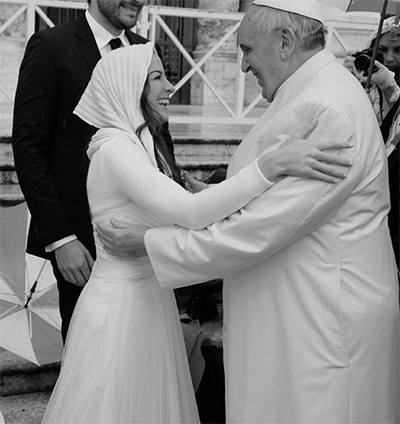 Melissa Ulloa smiles at Pope Francis after giving him a hug.