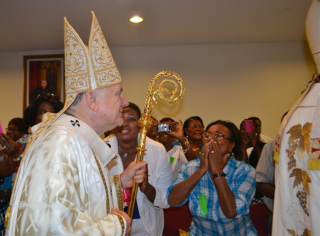 Parishioners react as Archbishop Thomas Wenski walks into Notre Dame d'Haiti Church for the dedication Mass.