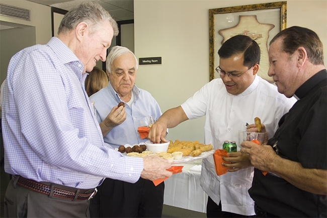 Host Msgr. Jude O'Doherty, pastor of Epiphany Parish, passes out some hors d'oeuvres at the start of the luncheon. With him, from left: Father Hernando Villegas, Father Elvis Gonzalez and Father Jairo Tellez.