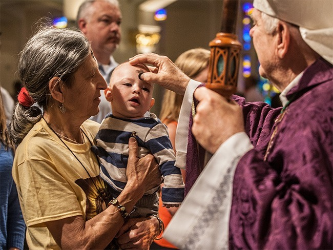 Archbishop Wenski places ashes on the forehead of Sean Tamburrino, 7 months old, as his grandmother, Maria Tamburrino, holds him.
