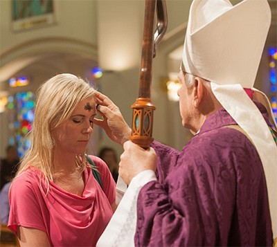 Agnieszka Wilczek receives ashes from Archbishop Thomas Wenski at St. Anthony Church, Fort Lauderdale.