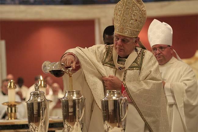 Archbishop Thomas Wenski pours balsam into the oil of chrism.