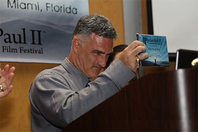 """Rafael Anrrich, the film festival's co-founder, presents the """"Inspiration"""" award to """"The Drop Box."""" Nicknamed """"the godfather"""" of the film festival, he works as a mental/behavioral health therapist."""