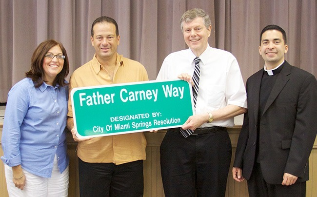 Miami Springs Mayor Zavier Garcia, center-left, and Tim Carney, brother to the late Father Joseph Carney, hold a replica of the street sign dedicated to the priest's memory. At left is Blessed Trinity School principal Maria Teresa Perez and at right is the parish administrator, Father Jose Alfaro.