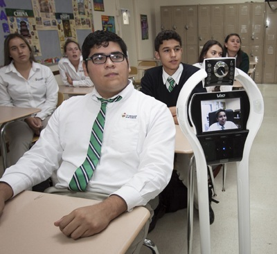 In a demonstration, incoming junior Kristopher Gonzalez (visible on the TV screen) participates in a St. Brendan High class via the school's rolling robot. It allows students to