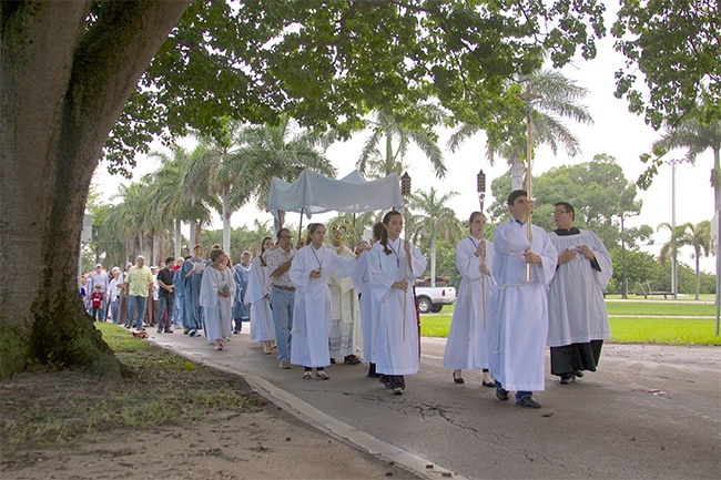 Father Jose Alfaro, Blessed Trinity's administrator, holds the monstrance and leads the eucharistic procession while members of the parish community hold the canopy and others process behind them.  The procession led parishioners from the church to the center of Miami Springs near the Circle. The entire route was nearly one and a half miles. The choir led the group in song and members of the Emmaus community led the group in the rosary.