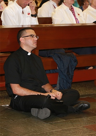 Newly ordained transitional Deacon Javier Barreto, from the Archdiocese of Miami, sits in front of the altar praying the rosary during the all night vigil on the solemnity of the Sacred Heart of Jesus and the feast of the Immaculate Heart of Mary.