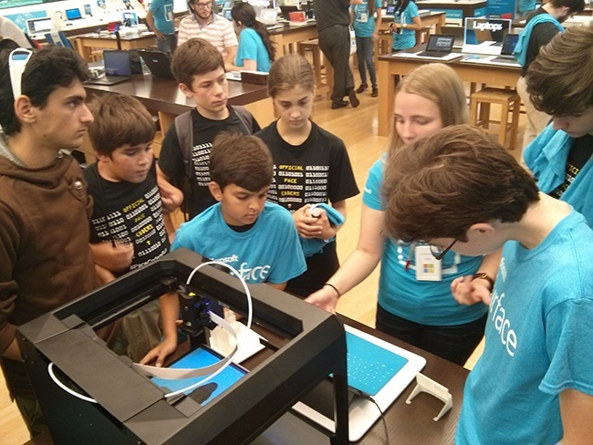 Geek Week attendees Antonio D'Agenzio, Joshua Dubon, Noah Florin, Eduardo Gabriel, Alexandra Perez, Andrew Sanchez, and Alexander Moore watch as a Microsoft Store employee (third from right) demonstrates a 3D printer.